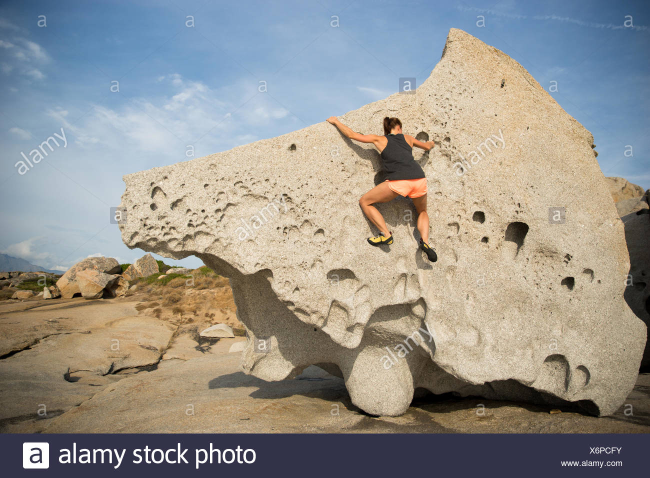 France, Corsica, Woman climbing on big single rock - Stock Image