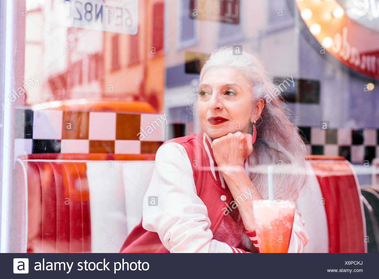 Mature woman in baseball jacket looking through window from 1950's diner - Stock Image