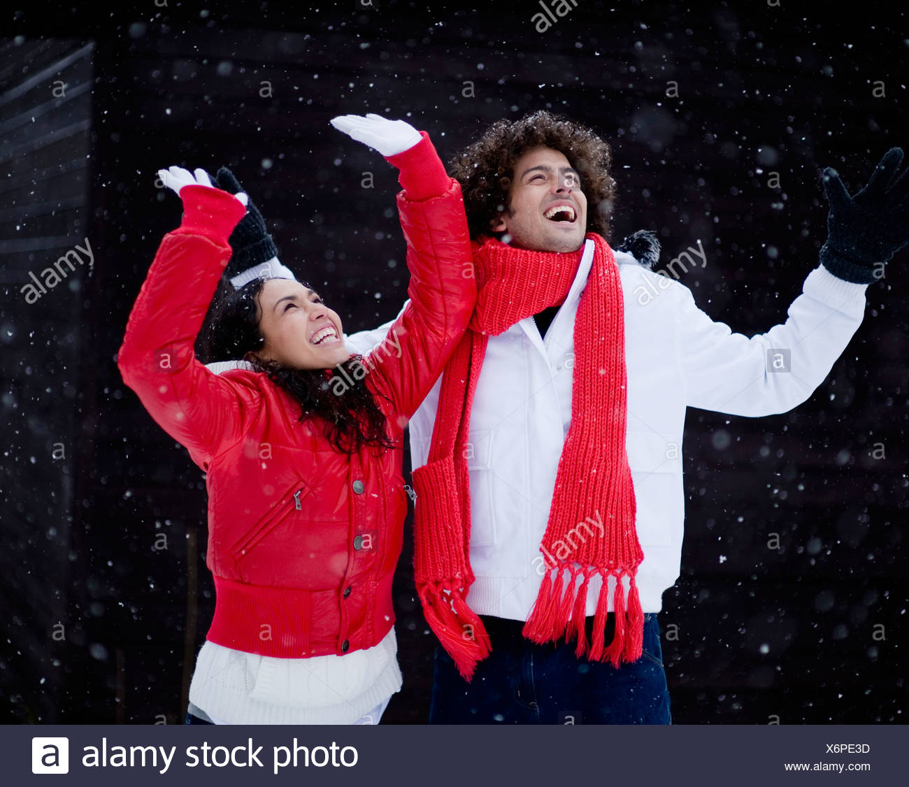 Happy young couple playing in snow on winter day - Stock Image