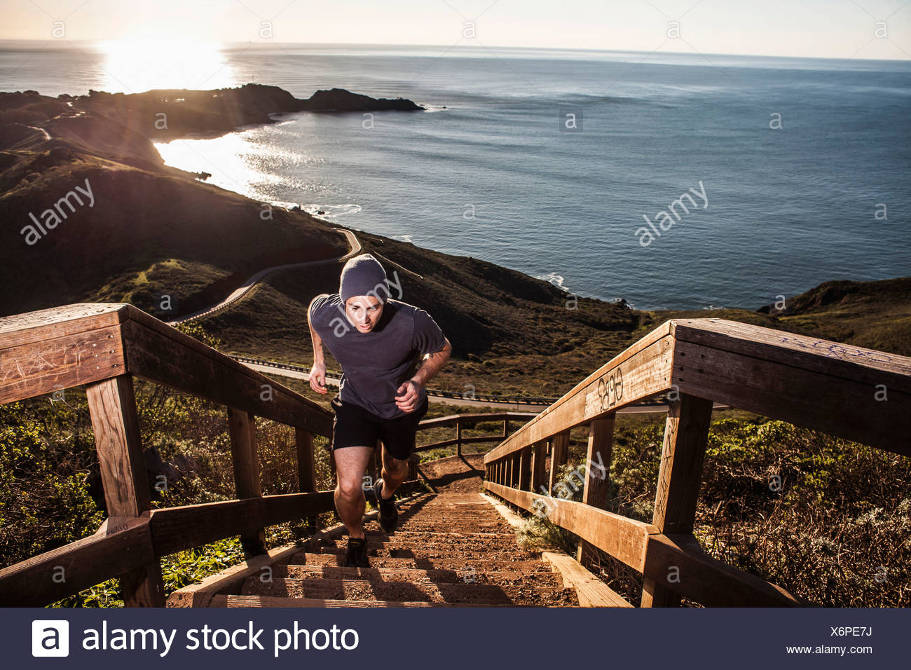 Young man running up coastal staircase at sunset - Stock Image