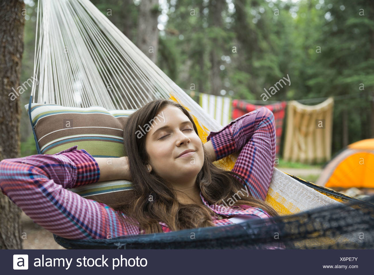 Teenage girl relaxing on hammock at campsite - Stock Image