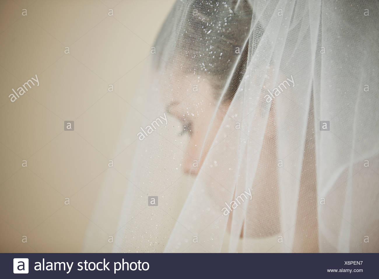 A young bride wearing a tiara and veil, looking down Stock Photo