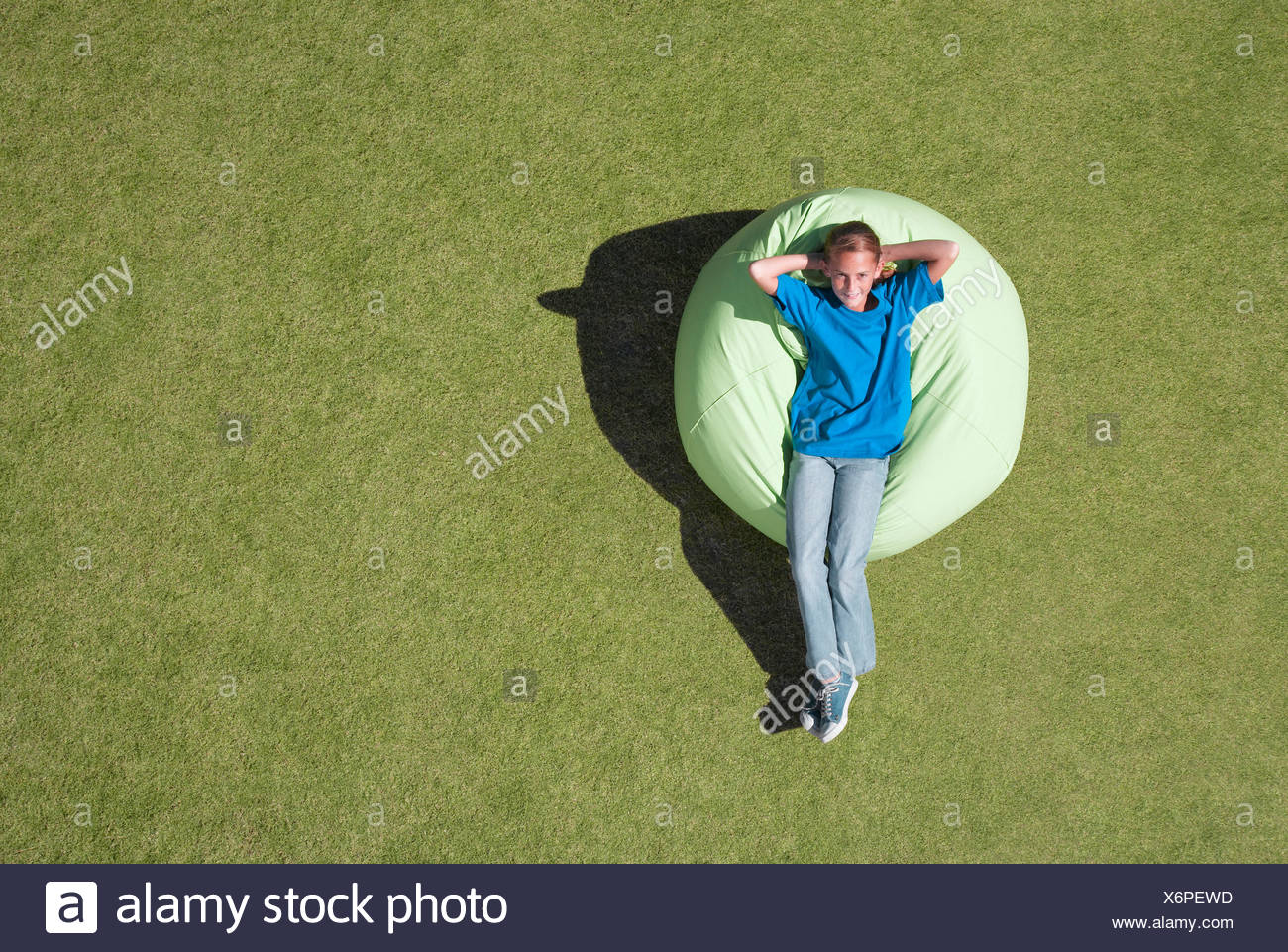 Young girl relaxing outdoors in bean bag - Stock Image
