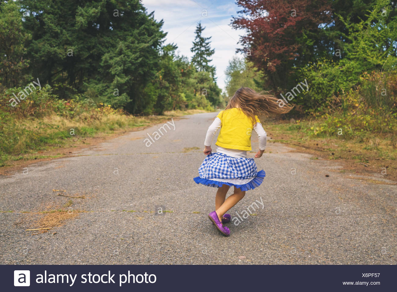 Girl spinning around on a road - Stock Image
