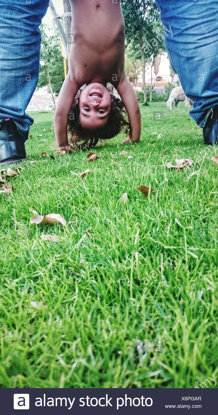 Low Section Of Man With Child Performing Handstand On Grassy Field - Stock Image