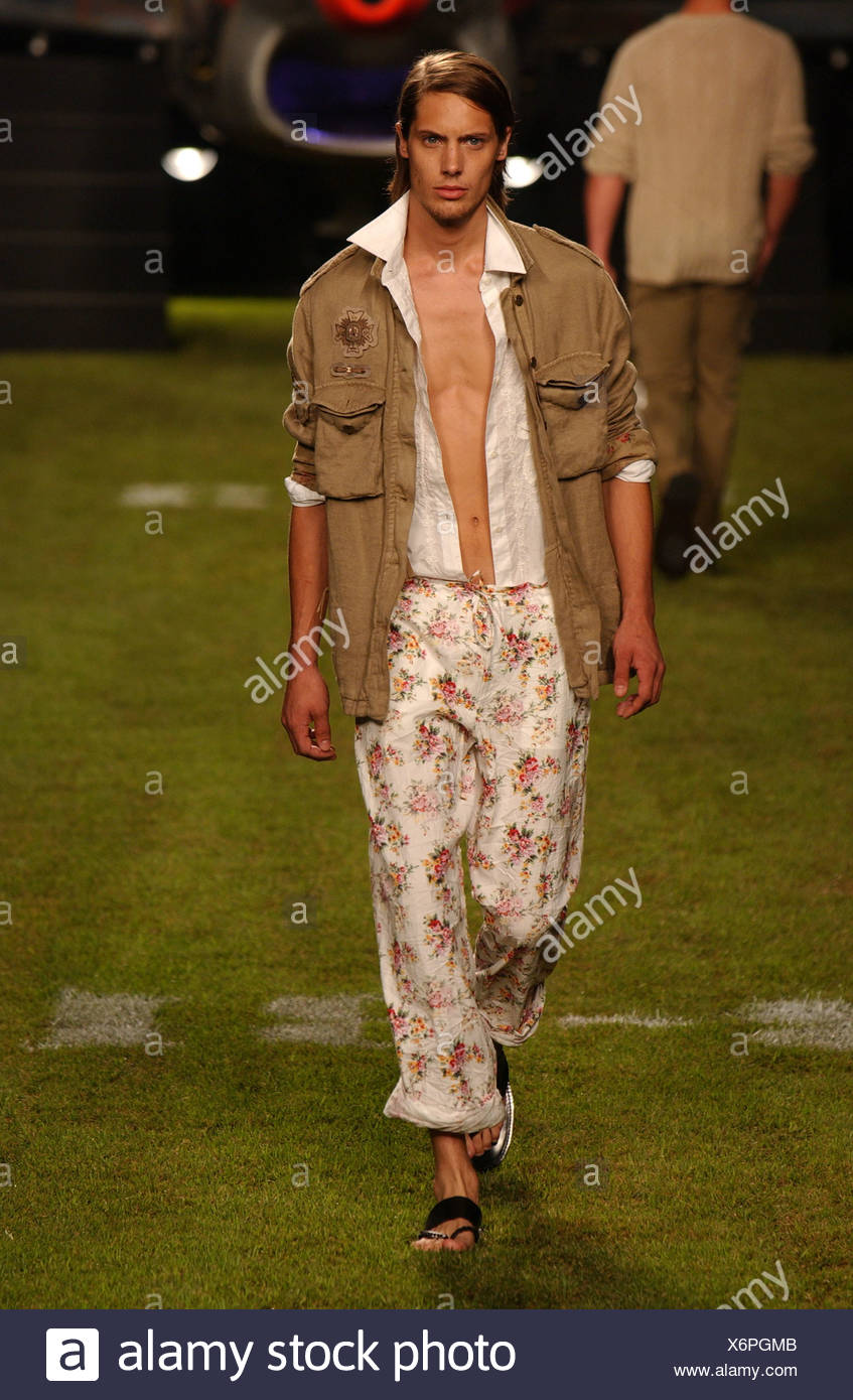 Iceberg Milan Menswear S S Male walking on green grass, wearing olive combat jacket over white shirt and rolled up flower print Stock Photo