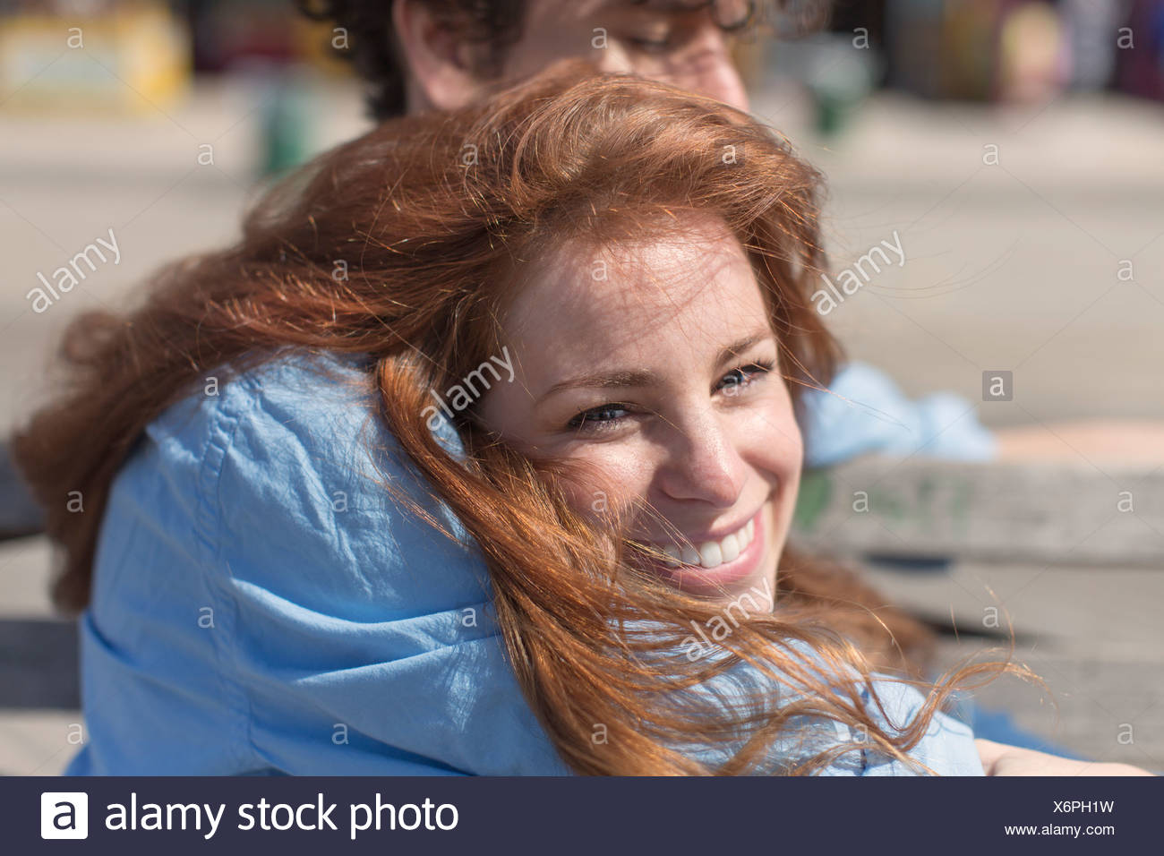 Close up portrait of young woman in boyfriends arms - Stock Image