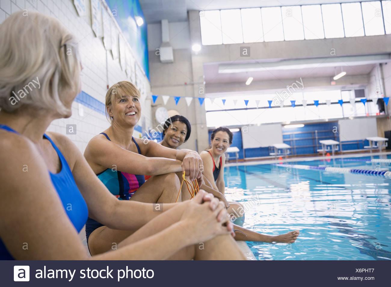 Women talking at indoor swimming pool - Stock Image