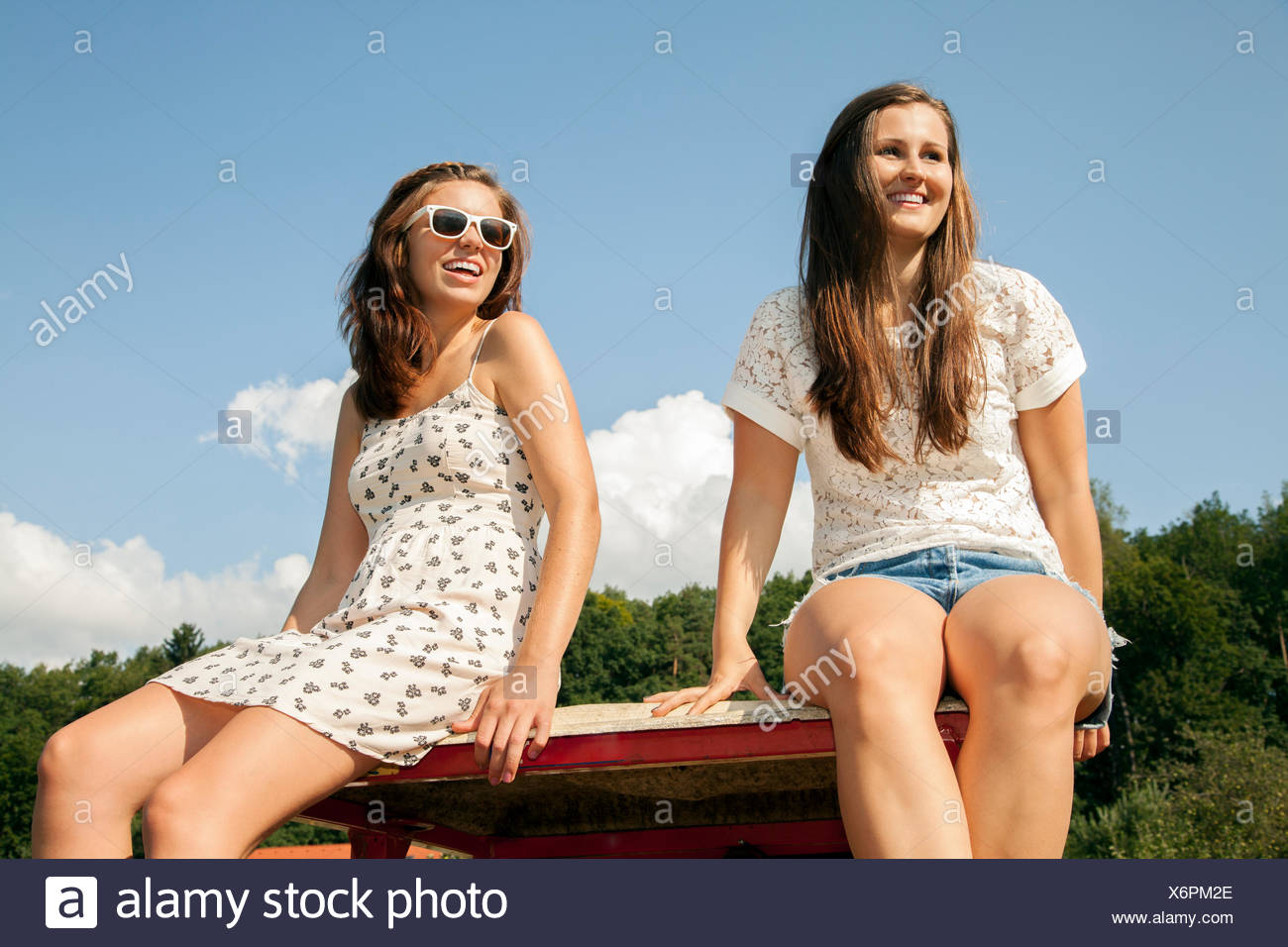 Two young women sitting in trailer - Stock Image