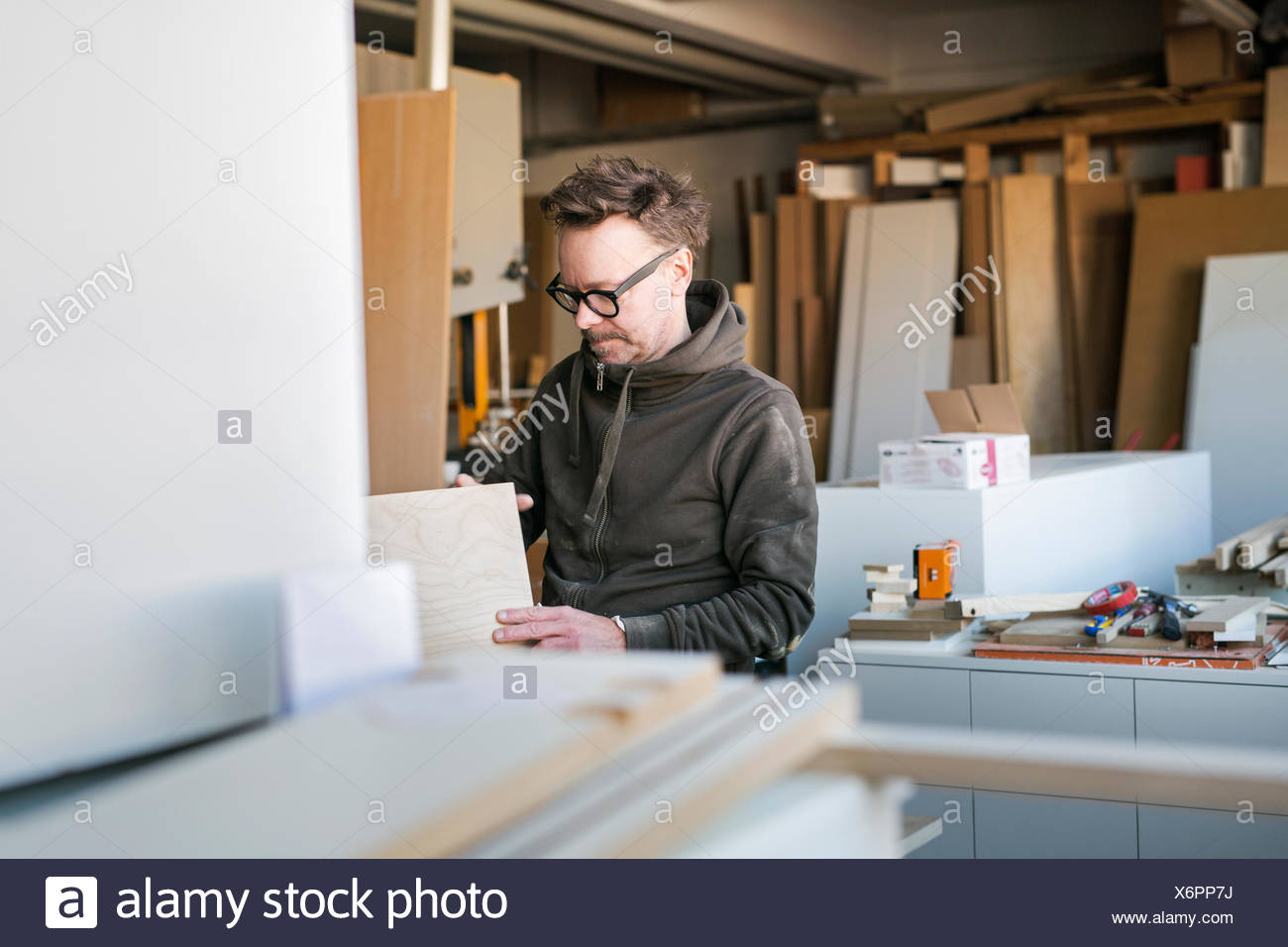 Carpenter with wood planks in workshop - Stock Image