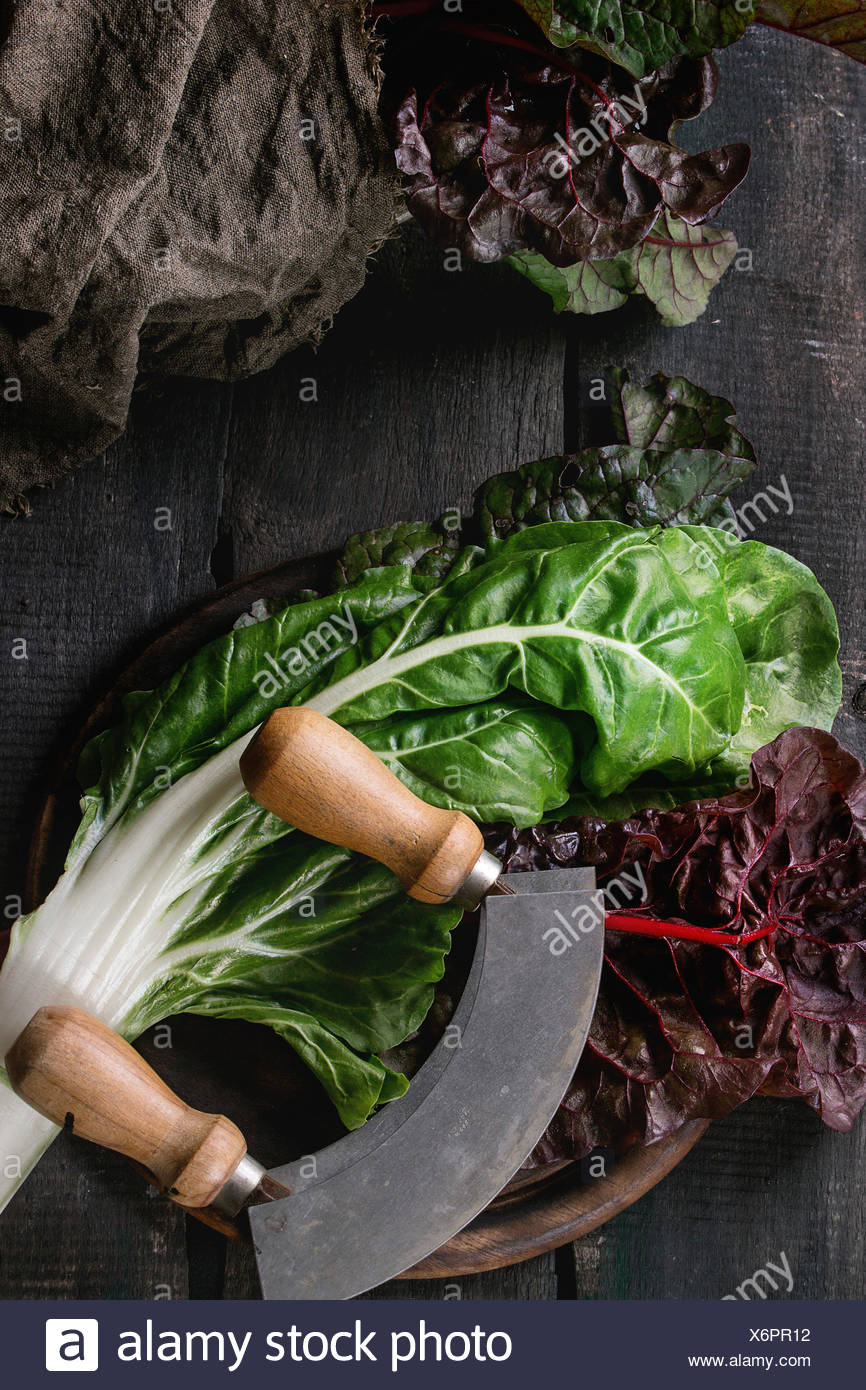 Variety of fresh chard mangold salad leaves on woode chopping board with vintage knife and sackcloth rag over old dark wooden ba - Stock Image
