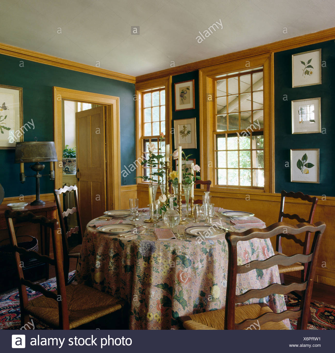 Antique Ladder Back Chairs At Circular Table With Floral Cloth In Dark Green Country Dining Room With Pale Woodwork Stock Photo Alamy