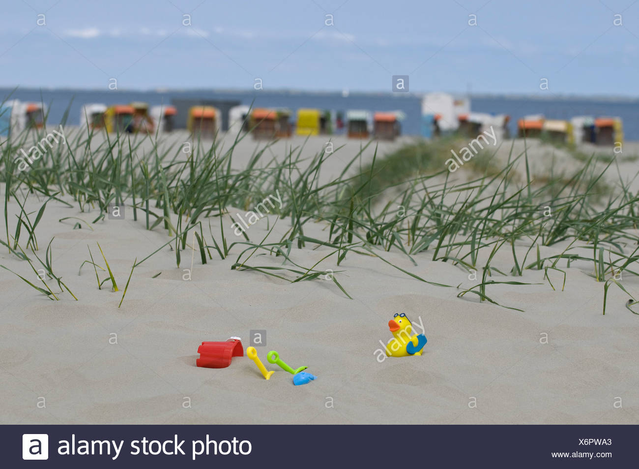 Holidays, children's toys on a sand dune in front of roofed wicker beach chairs on a beach and the sea, Norddeich, Norden - Stock Image