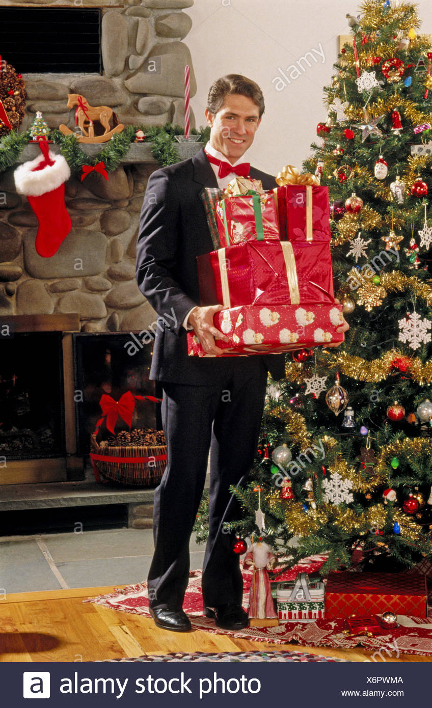 Man in tux with Christmas presents - Stock Image