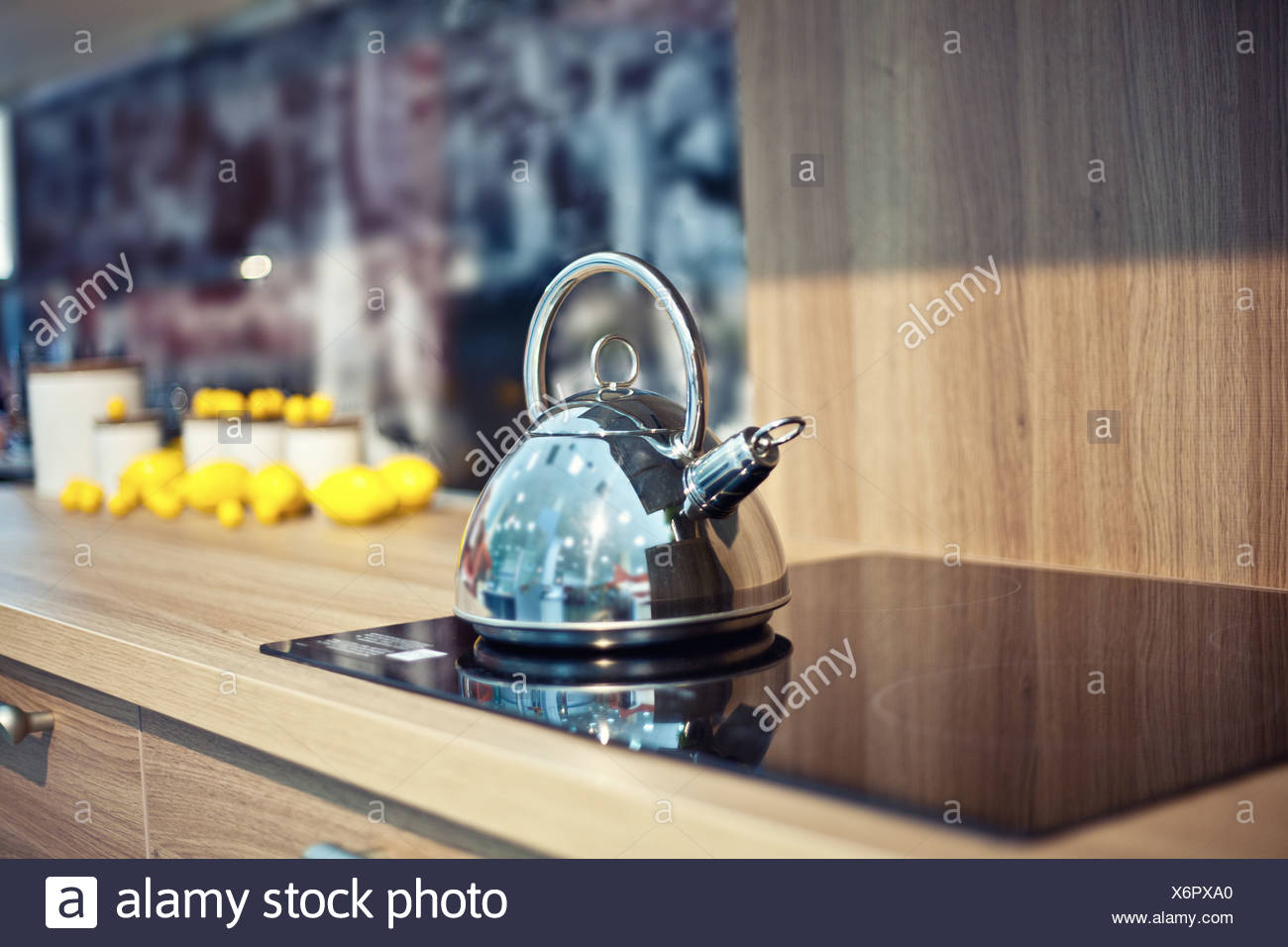 Shiny tea kettle on the kitchen table (beautiful diepth of field effect) - Stock Image