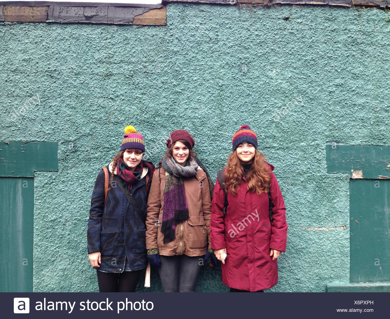 Three women standing against a wall - Stock Image