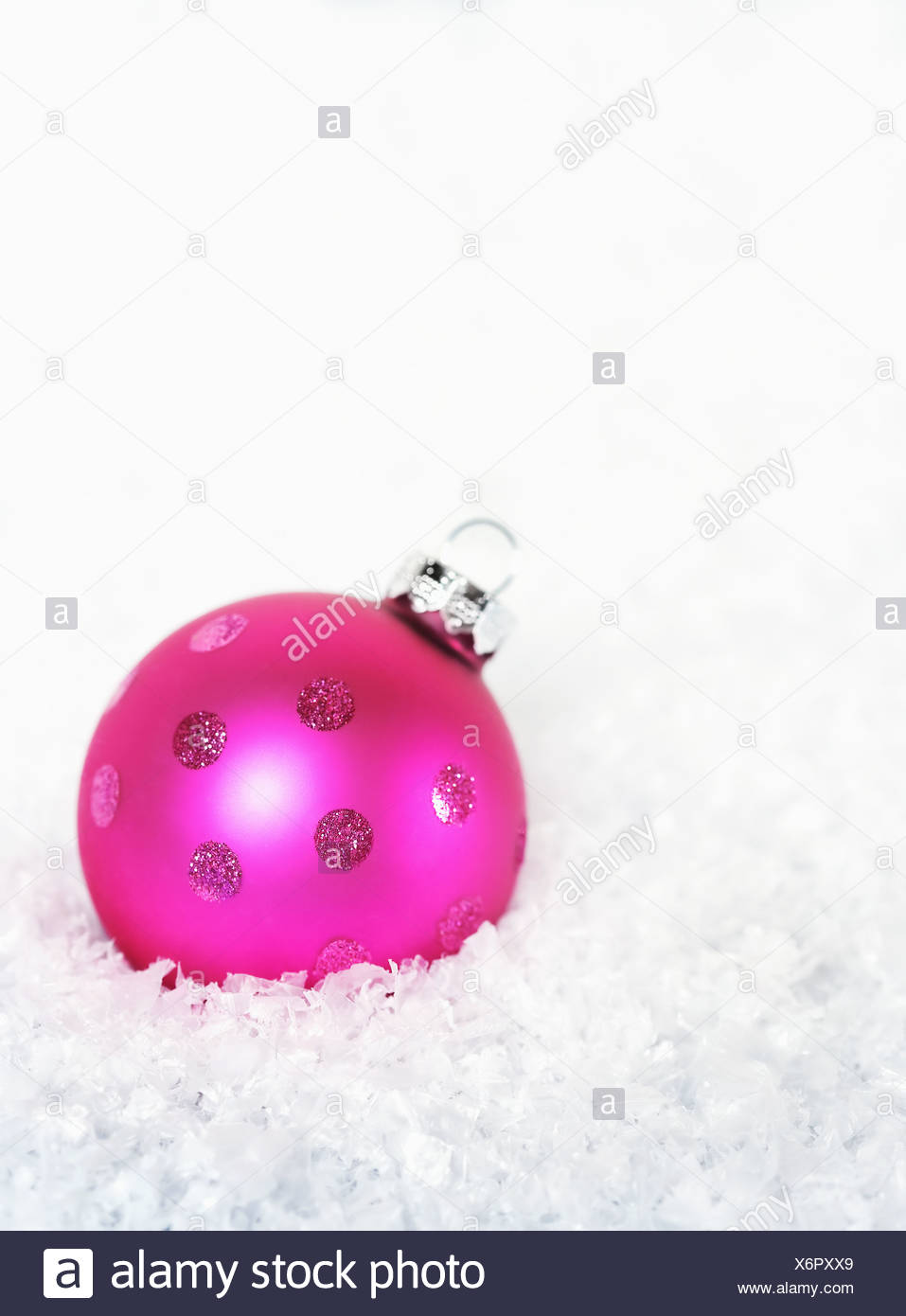 Pink Christmas bauble on snow - Stock Image