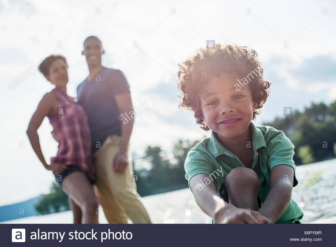 A family, parents and son by a lake in summer. Stock Photo