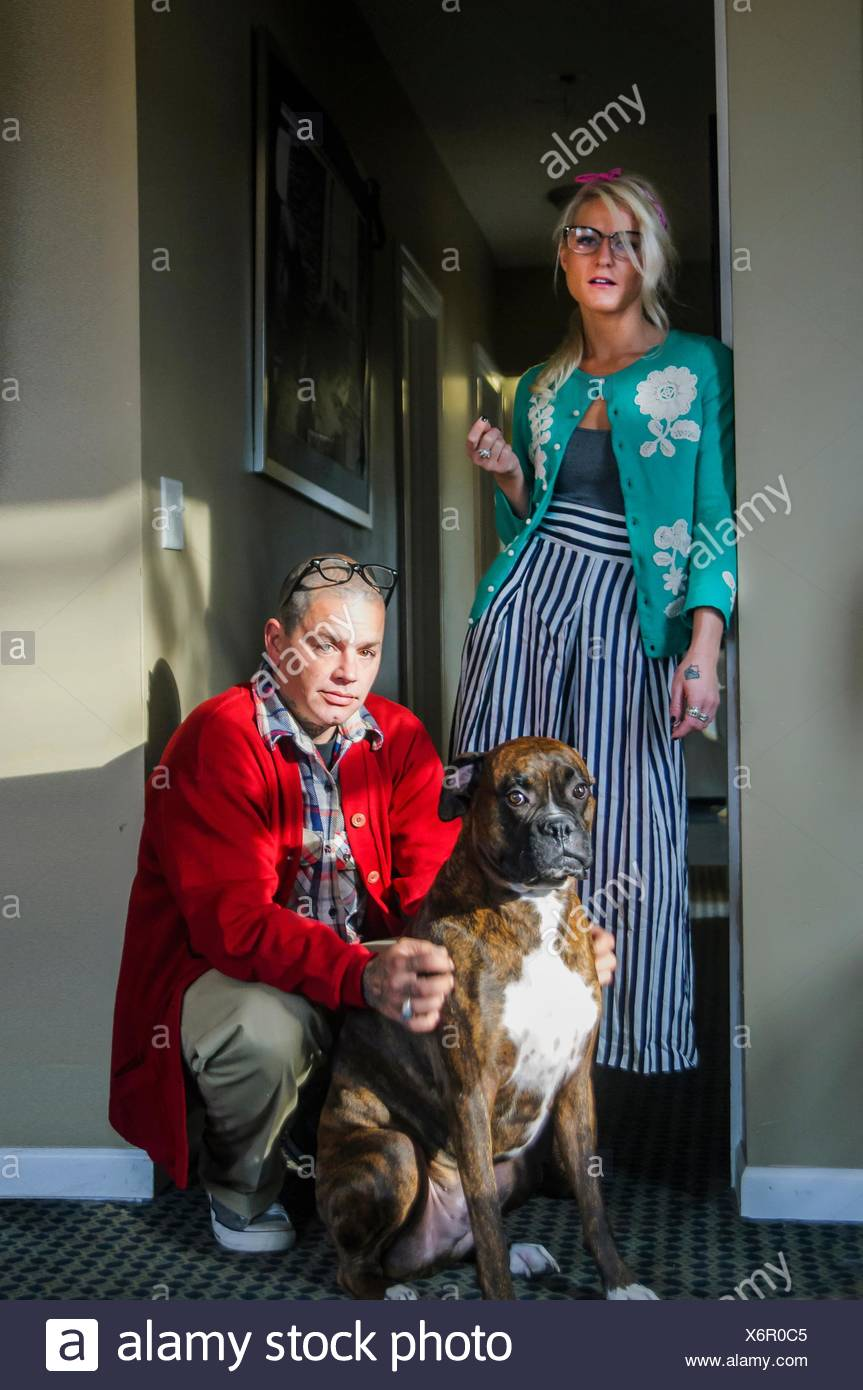 Couple in hallway with boxer dog looking at camera - Stock Image