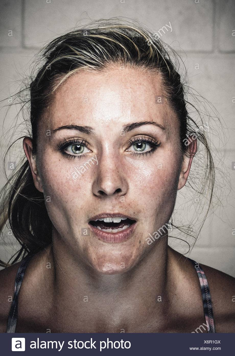 Portrait of sweaty young woman with open mouth after workout - Stock Image
