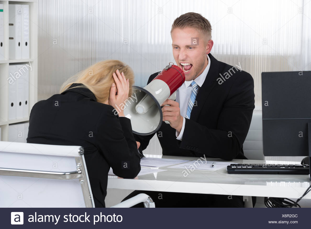 Boss Shouting At Businesswoman Through Loudspeaker In Office Stock Photo
