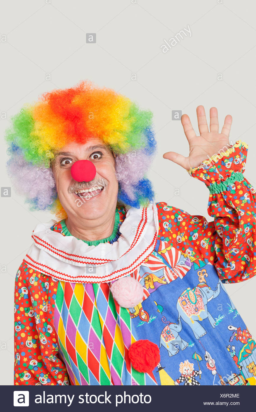 Portrait of cheerful senior male clown waving hand over gray background - Stock Image