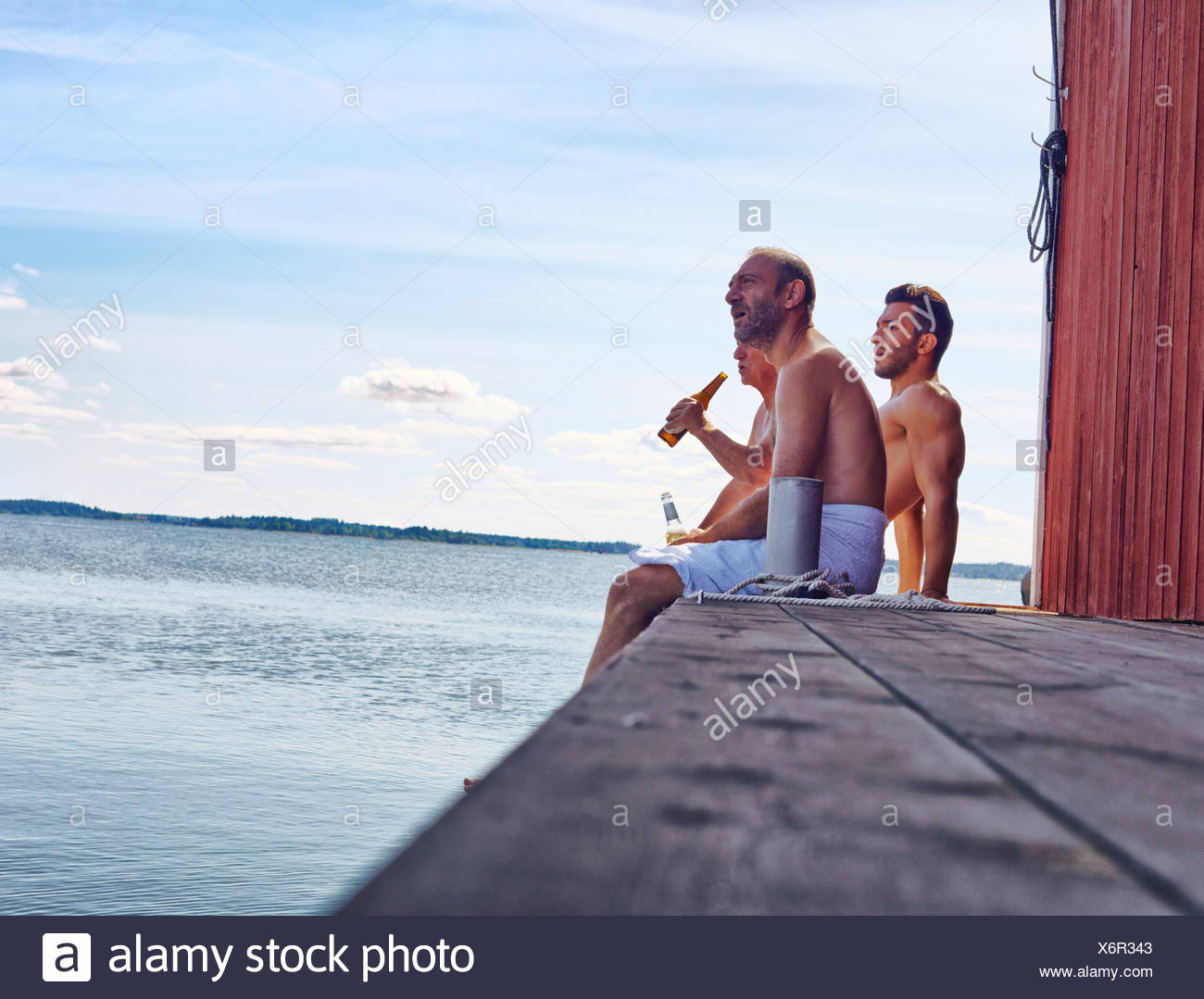 Three male friends sitting outside sauna enjoying beer Stock Photo