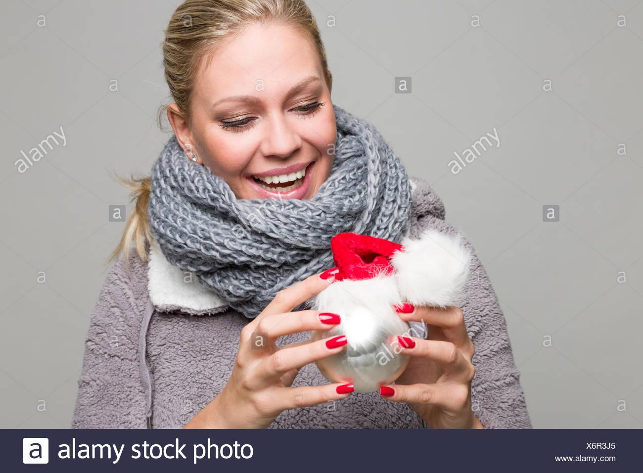 Frau mit langen blonden Haaren hält vor sich eine Christbaumkugel in weiß und silber mit einer kleinen Weihnachstmütze darauf - Stock Image