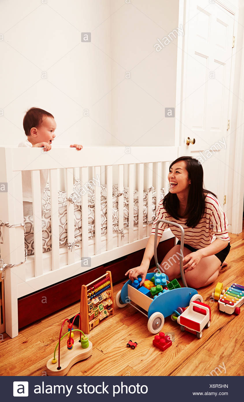 Mother tidying up toys, baby boy looking over crib - Stock Image