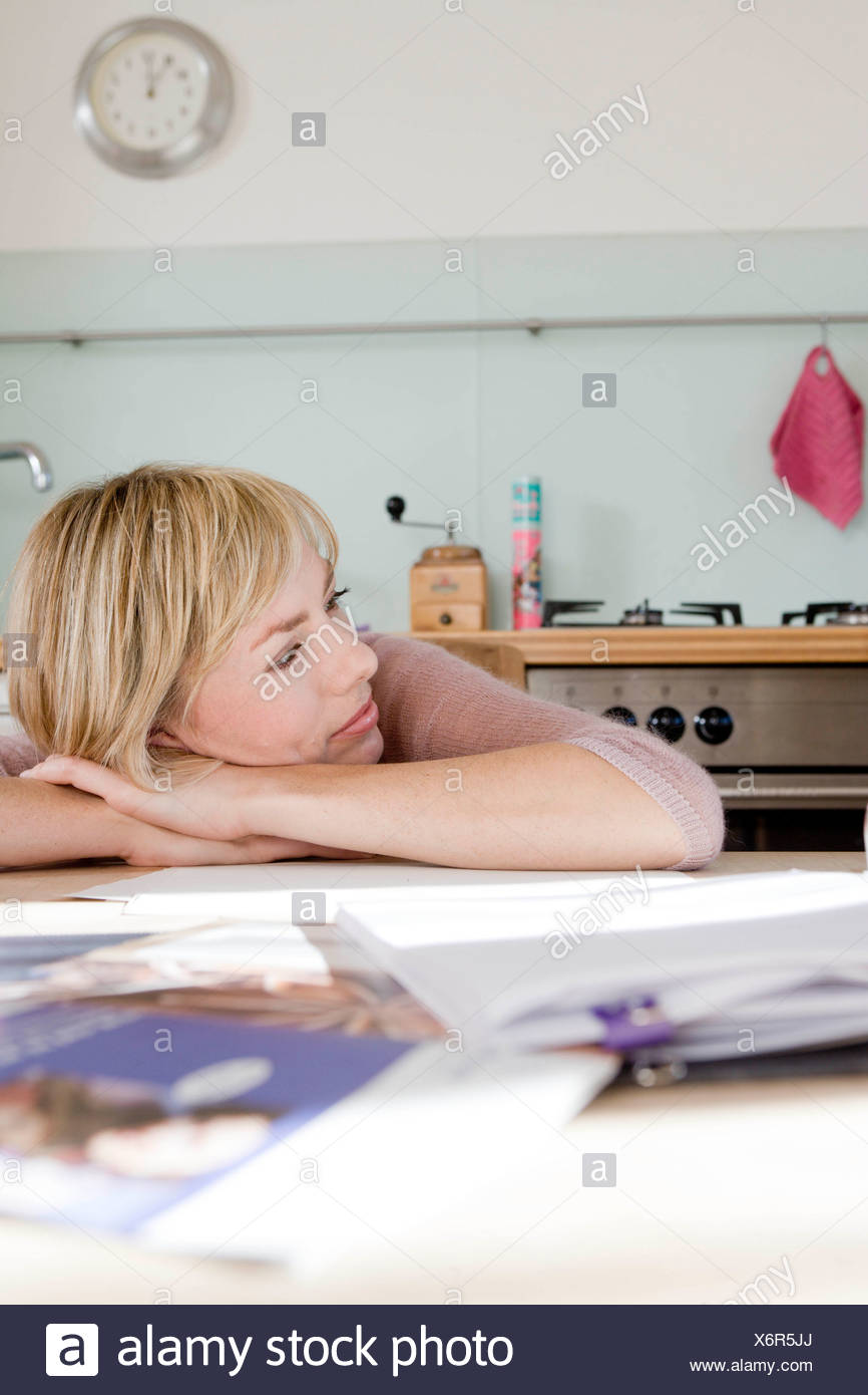 Woman resting head on kitchen table - Stock Image