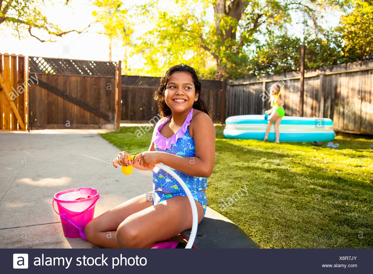 Girl filling balloon with water in garden - Stock Image