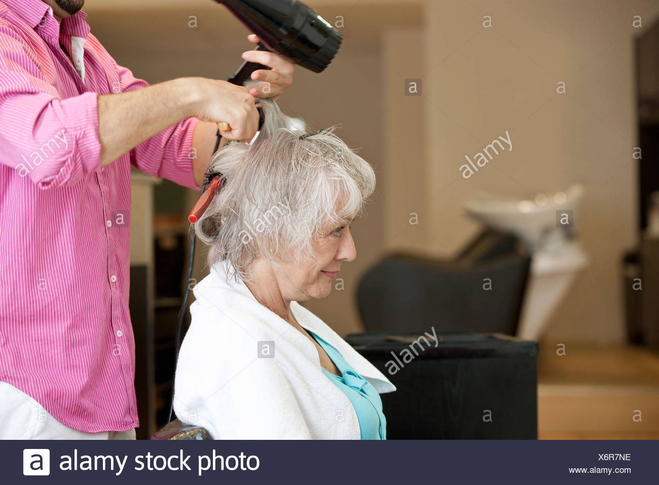 A senior woman having her blow dried at a hairdressing salon - Stock Image