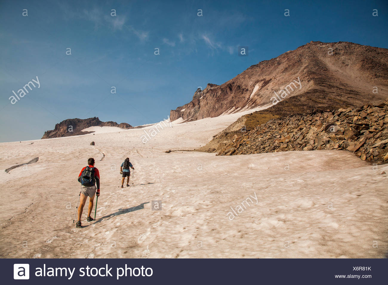 Two climbers ascend a snowfield while climbing Glacier Peak in the Glacier Peak Wilderness in Washington. - Stock Image