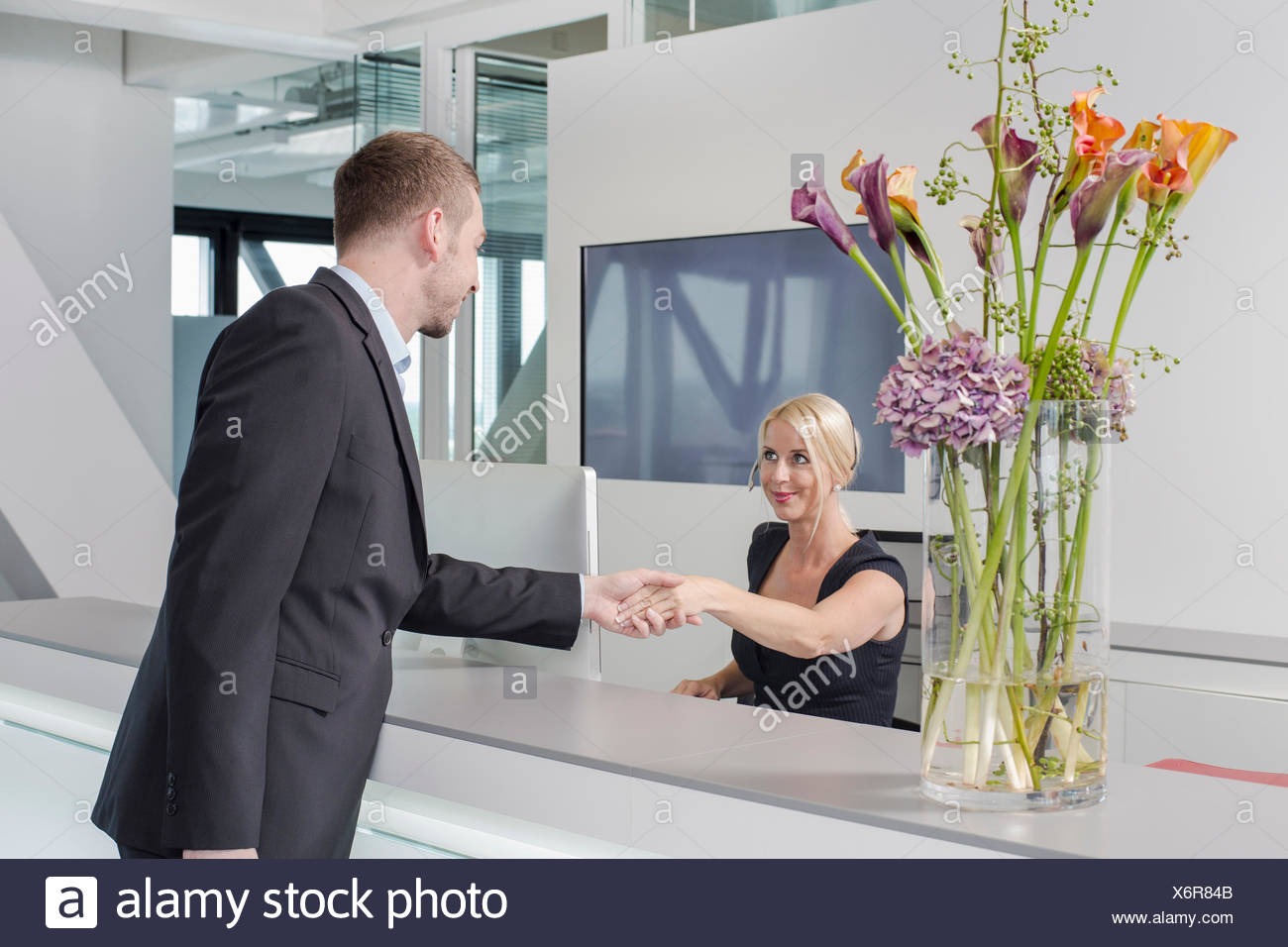 Man shaking hands with female receptionist - Stock Image