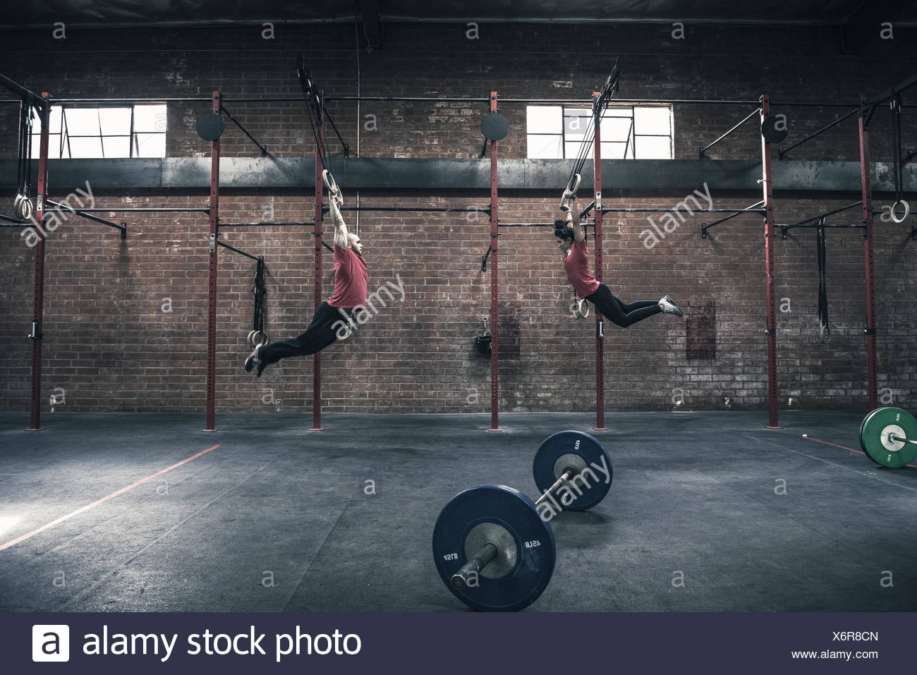 Young man and woman swinging on gym rings in gym Stock Photo