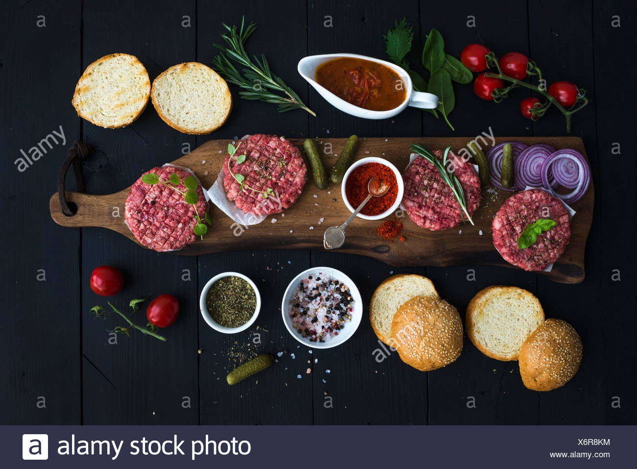 Ingredients for cooking burgers. Raw ground beef meat cutlets on wooden chopping board, red onion, cherry tomatoes, greens, pick - Stock Image
