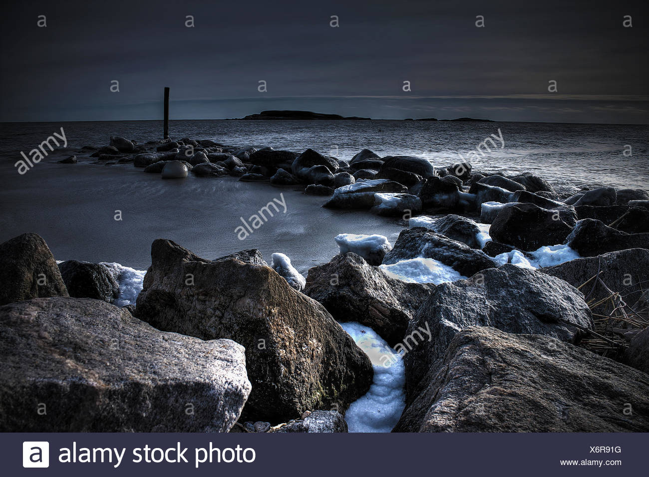 Rocky breakwaters at beach - Stock Image