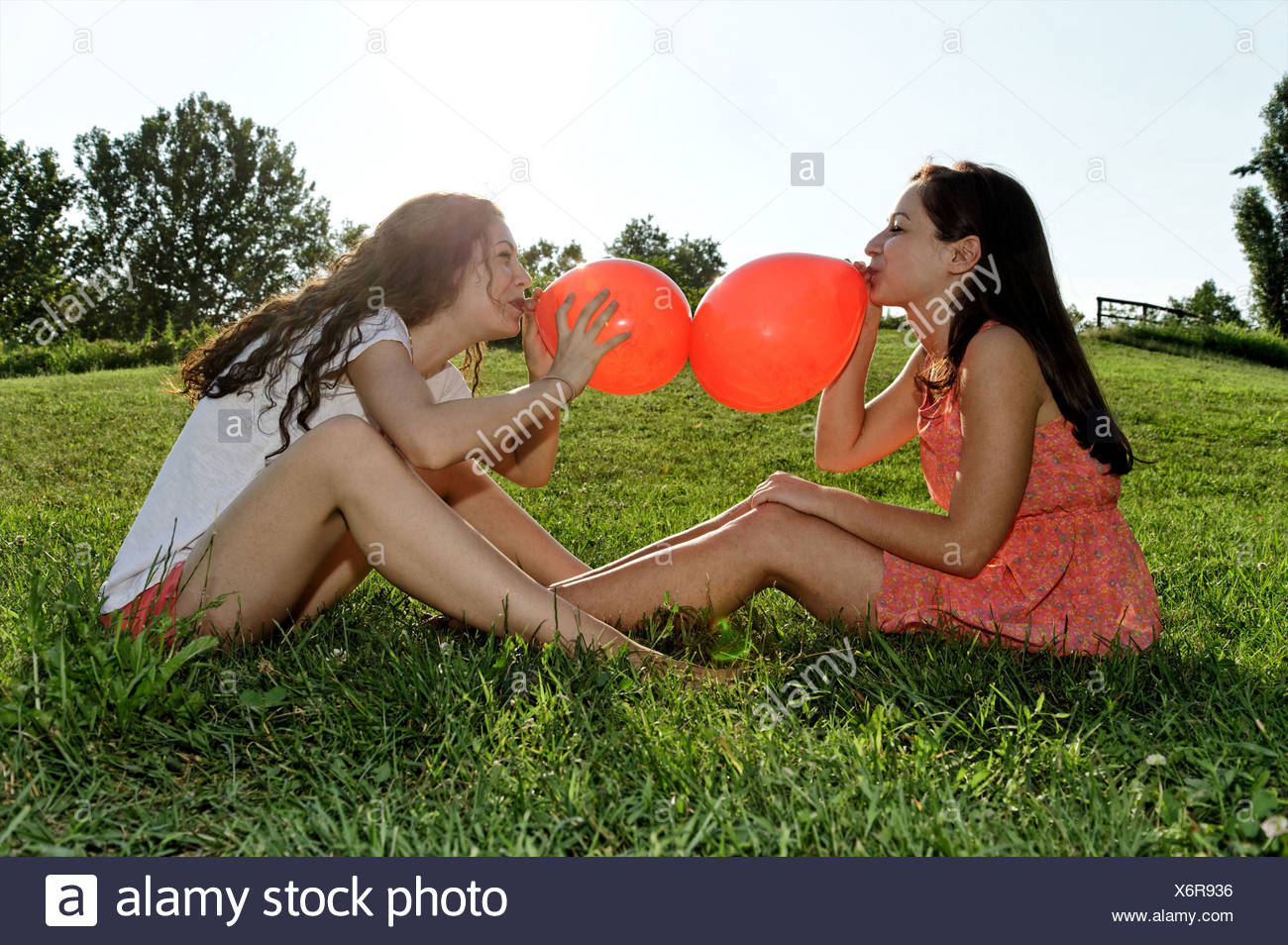 Two young women sitting on grass bowing up red balloons - Stock Image