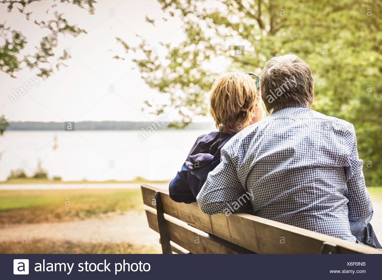 Rear view of adult couple on lakeside park bench - Stock Image