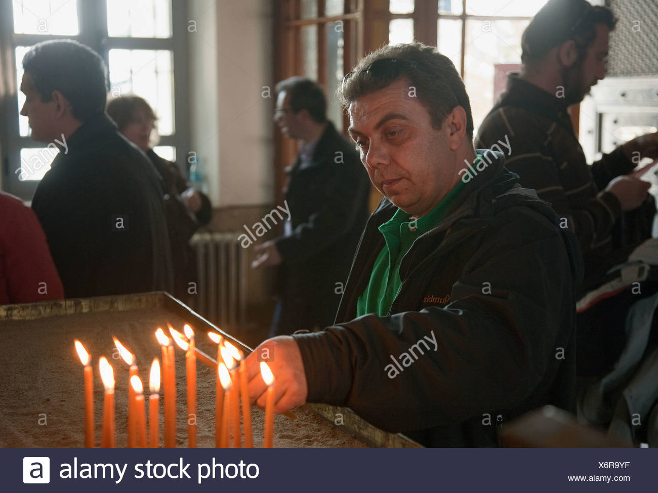 Believer lighting a candle in church, Heybeliada, Turkey - Stock Image