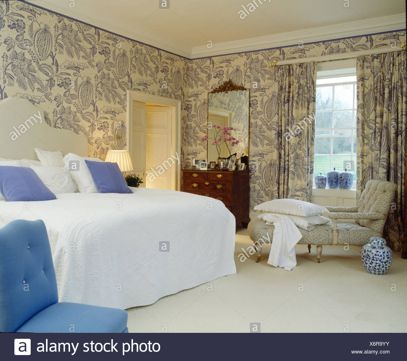 Blue+white wallpaper and matching curtains in country bedroom with chaise longue and bed with white quilt - Stock Image