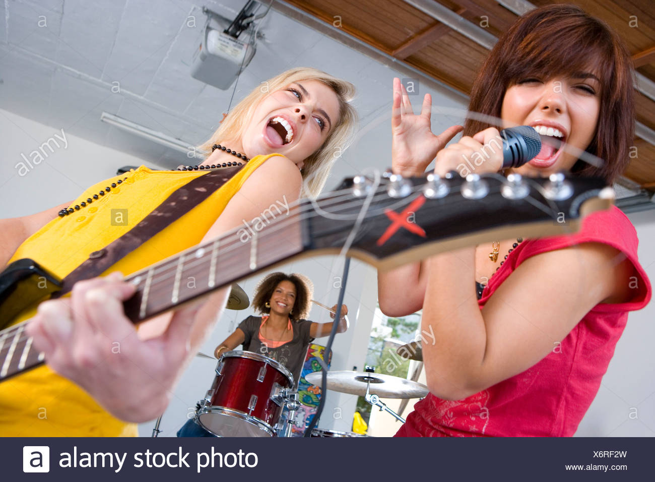 Three teenagers  in garage band, teenage girls singing and playing guitar in foreground - Stock Image