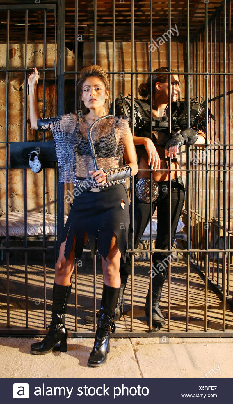 woman science future guard brig jail cell captivity costume escape cage whip - Stock Image