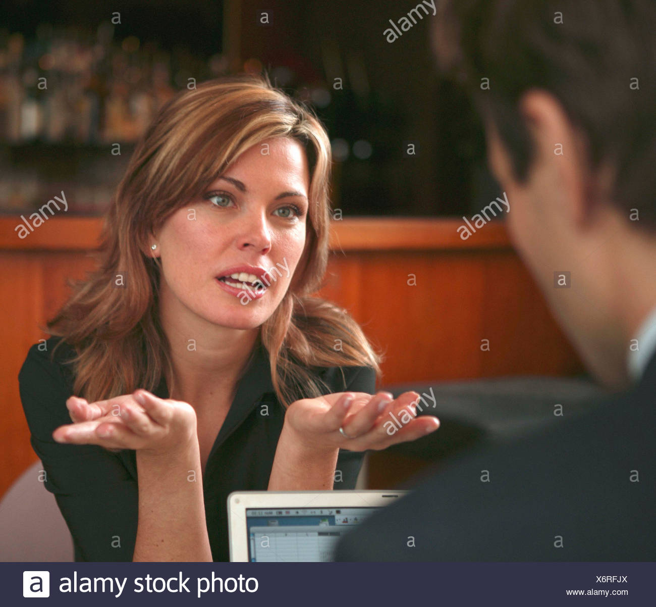 A businesswoman and man having a meeting in a hotel bar - Stock Image