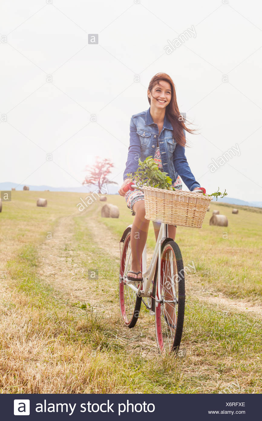 Teenager riding bicycle on field, Roznov, Czech Republic - Stock Image