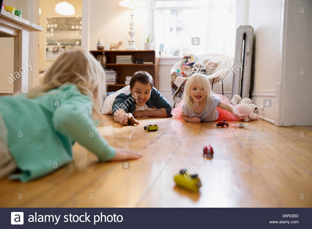 Father and daughters racing toy cars on floor - Stock Image