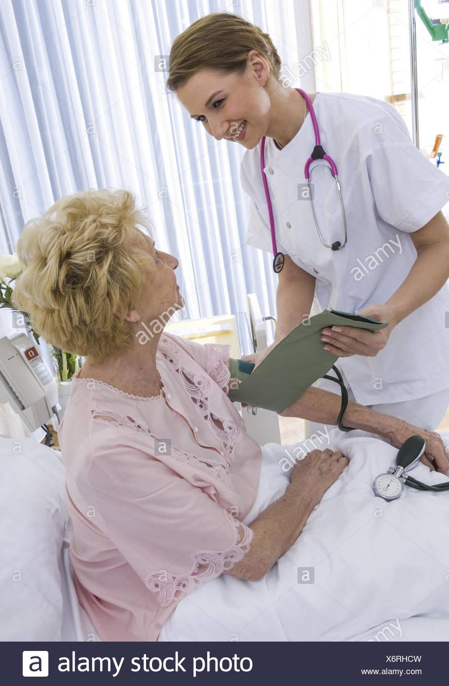 Krankenschwester bei aelterer Patientin im Krankenhaus (model-released) - Stock Image