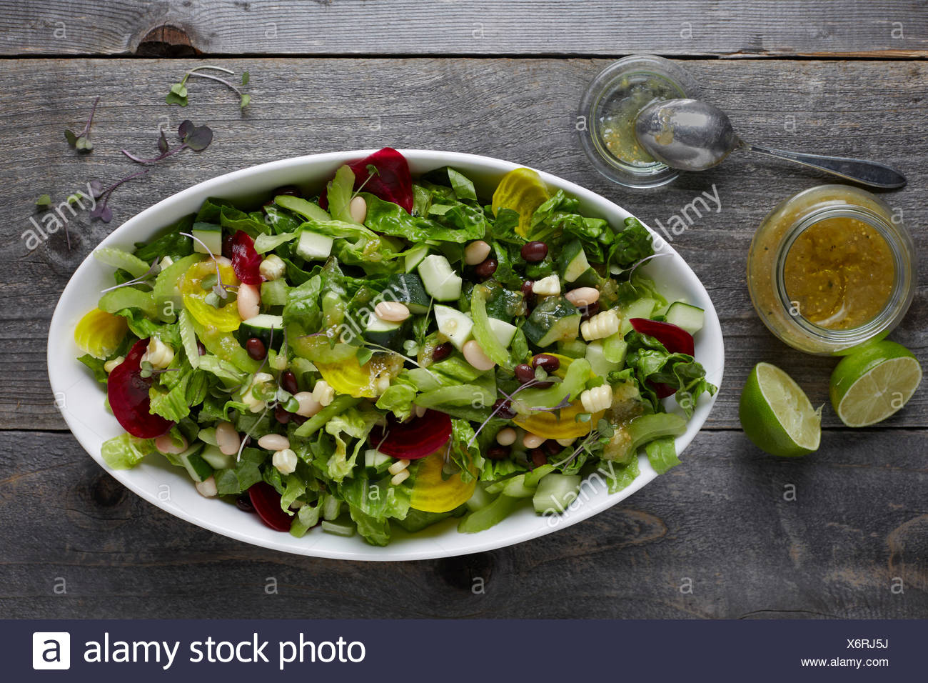 White ceramic bowl full of fresh mixed lettuce salad with healthy toppings, shot areal view with vinaigrette and limes beside th - Stock Image