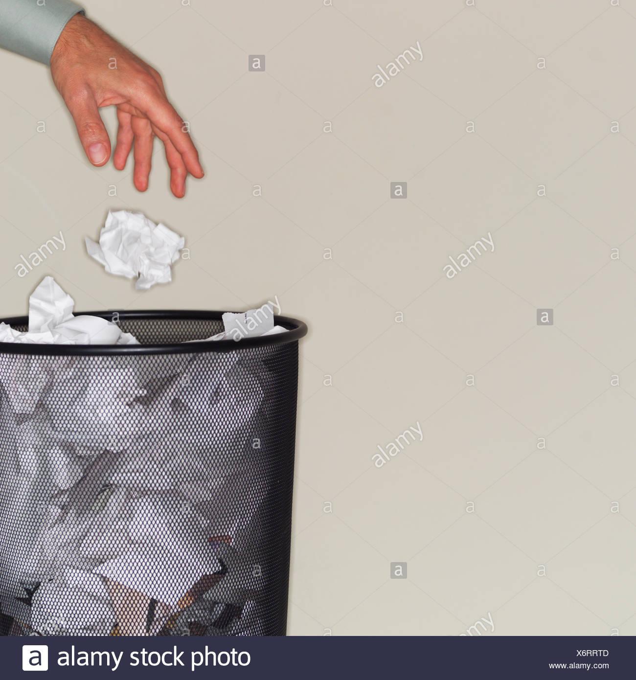 Man throwing paper balls into wastepaper basket Stock Photo