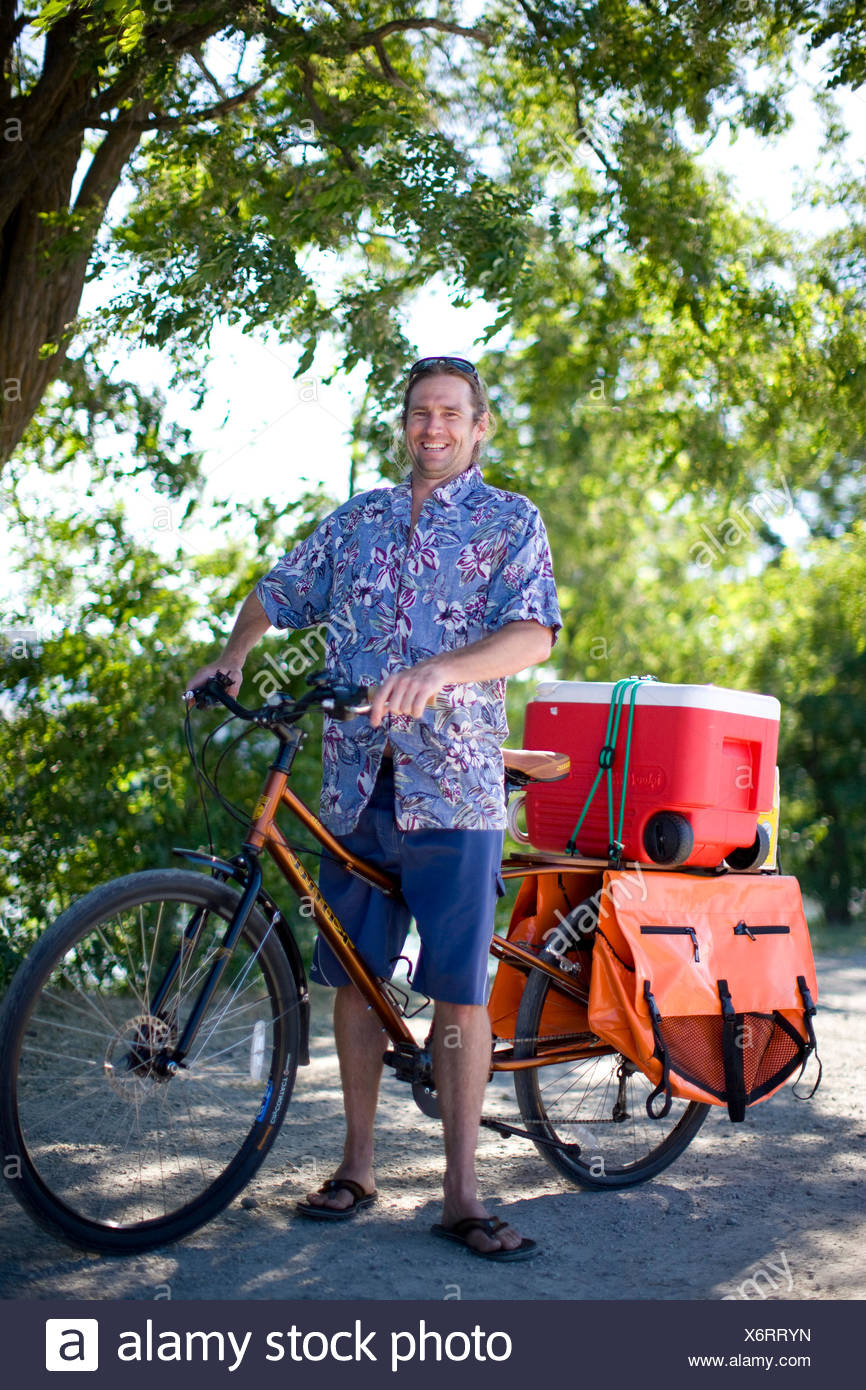 Portrait of adult male cyclist using his bike to haul supplies - Stock Image
